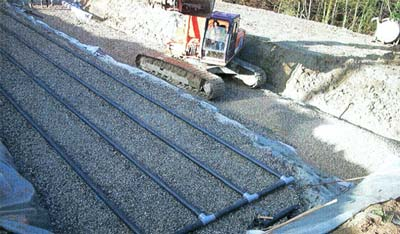 Station d'assainissement rustique de type fosse septique toutes eaux, filtre pouzzolane, filtre à sable vertical drainé étanche et rejet dans une zone naturelle de dissipation.